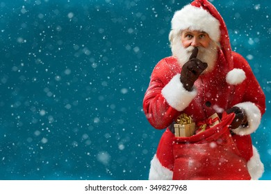 Santa Claus with huge red sack keeping forefinger by his mouth and looking at camera / Merry Christmas & New Year's Eve concept / Closeup on blurred blue background. Copy space