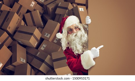 Santa Claus indicates a space for the Christimas present, with ready packages on background