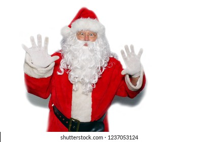 Santa Claus. Isolated on white. Room for text. Santa holds his hands up and looks shocked or scared as if he is being robbed. Santa up against a wall with hard shadows.
