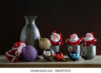 Santa claus joyful in Christmas day with Sake whisky of Japan and color ball on the plank