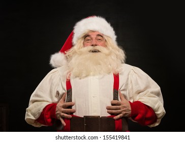 Santa Claus laughing loudly against dark background
