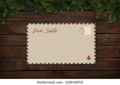 Santa Claus letter on wooden table with christmas tree branches