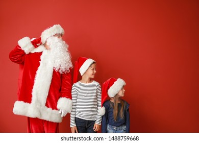 Santa Claus and little children on color background