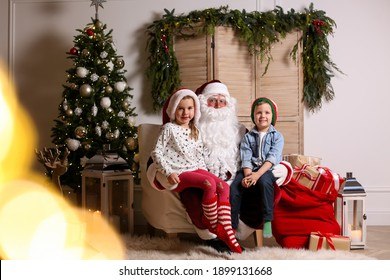 Santa Claus with little children in photo zone decorated for Christmas