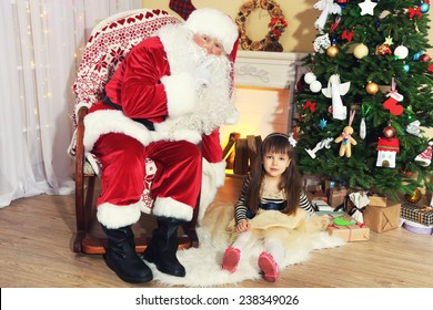 Santa Claus with little cute girl near  fireplace and Christmas tree at home