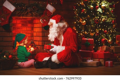 Santa Claus and little elf with a magic gift for Christmas