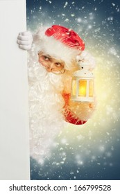 Santa Claus looking from behind white blank banner holding a shining lantern