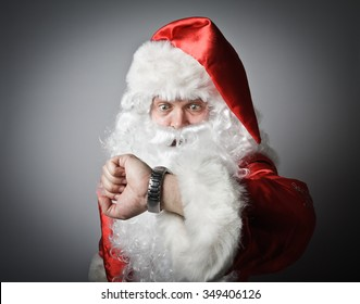 Santa Claus is looking at his wristwatch. Concept of being late.