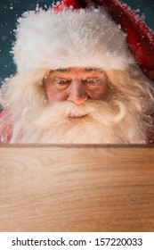 Santa Claus looking into wooden box outdoors. Light is coming from inside to his face. Opening Christmas magic concept.