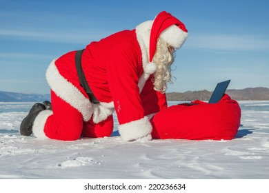 Santa Claus lying on the snow, looking at laptop news, shooting was conducted in a sunny day on lake Baikal