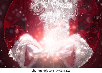 Santa Claus with magic Christmas lights in hands