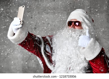 Santa Claus make selfie with mobile cellphone under snow confetti. New year and Merry Christmas and happy holidays concept