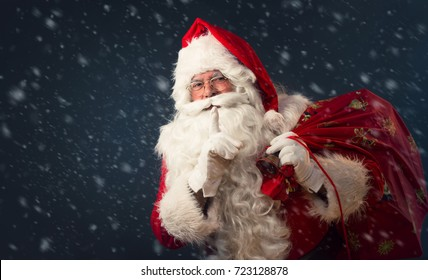 Santa Claus making a silence gesture, on dark background