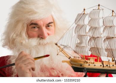 Santa Claus making toys. Painting and coloring wooden ship