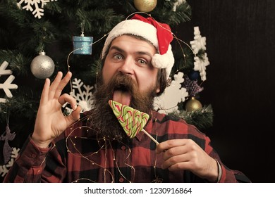 santa claus man in hat at decoration. Winter holiday and xmas. Party celebration and blowjob. Christmas man with beard on happy face ok gesture and lollipop. New year guy lick candy or sweet.