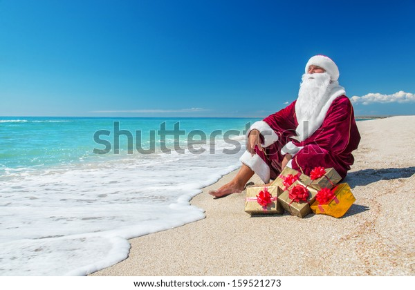 Santa Claus with many golden gifts relaxing on sea beach  - christmas  or happy new year concept
