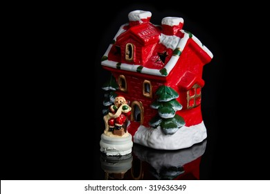 Santa Claus near decorated house isolated on black