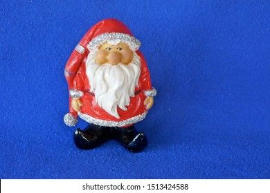Santa Claus. Nicholas. Christmas time. A cute little garden gnome in Santa Claus costume and red bonnet. Close up, isolated on blue background. (Not copyrighted)