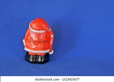 Santa Claus. Nicholas. Christmas time. A cute little garden gnome in Santa Claus costume and red bonnet.  Rear view. Close up, isolated on blue background. (Not copyrighted)