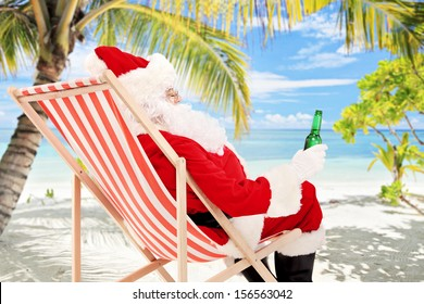 Santa Claus on a beach chair drinking beer and enjoying on a sunny day, on a tropical beach