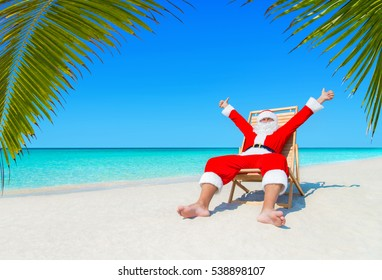 Santa Claus on beach chair at ocean tropical beach sand thumbs up positive hands gesturing under palm tree leaves. Happy New Year and Merry Christmas holidays travel destinations concept