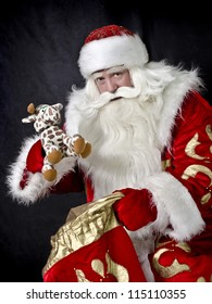 Santa Claus on a black background gives a gift