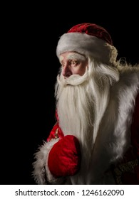 Santa Claus and Santa Claus on a black background. Santa Claus and Santa Claus majestic, looking amazed at the side, in profile against a black background.