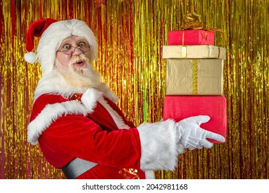 Santa Claus on golden foil backdrop. Emotional senior male model old man with a natural white beard in the role of Father Christmas bringing wrapped magic boxes Xmas gifts.