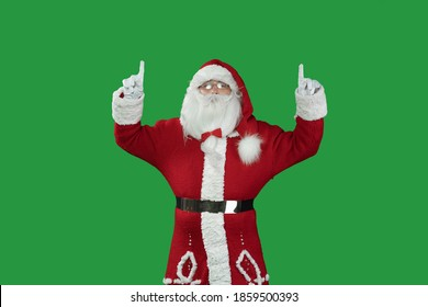 santa claus on a green background is pointing with two index fingers upwards at an empty space for the text. Copy space.