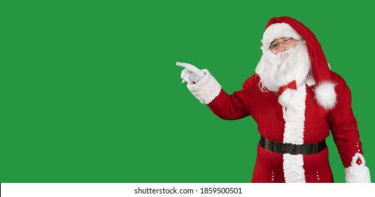 santa claus on a green background stands points a finger at an empty space for the text. Copy space.