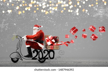 Santa Claus on scooter delivering Christmas or New Year 2020 gifts at snowy gray background