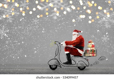 Santa Claus on scooter delivering Christmas or New Year gifts at snowy gray background