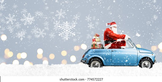 Santa Claus on scooter delivering Christmas or New Year gifts at snowy blue background