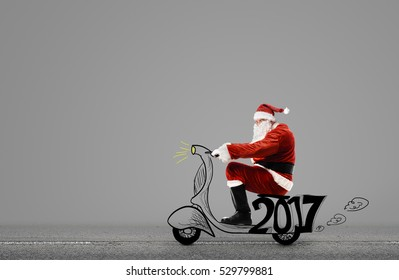 Santa Claus on scooter driving at gray background