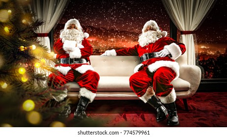 Santa claus on sofa in interior with big window and city landscape .