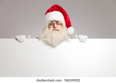 santa claus on top of a blank board on grey background
