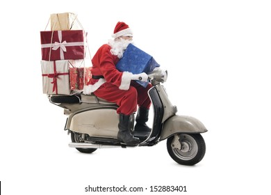 Santa Claus on vintage scooter with stack of christmas presents, isolated on white