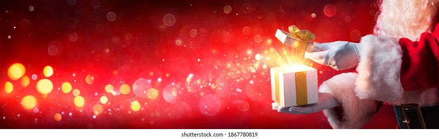 Santa Claus Opening Christmas Present With Shiny Stars