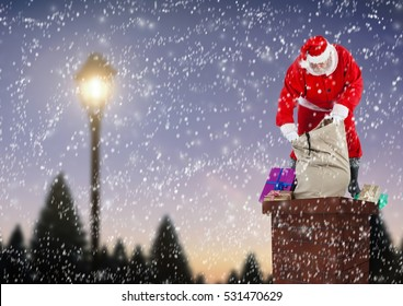 Santa claus opening gift sack on top of house chimney during snowfall