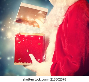 Santa Claus Opening a red Christmas Present in a Night