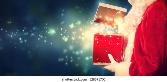 Santa Claus opening a red Christmas present at night
