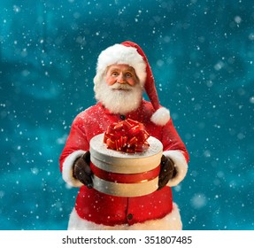 Santa Claus outdoors in snowfall carrying gifts to children / Merry Christmas & New Year's Eve concept / Closeup on blurred blue background.