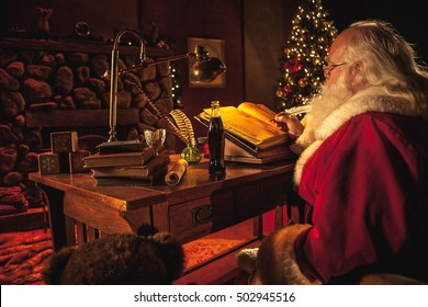 Santa Claus over the shoulder as he works on his naughty or nice list in his workshop at the northpole