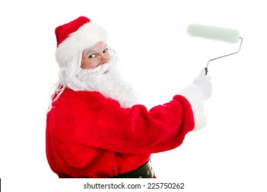 Santa Claus with a paint roller, working on a home improvement project.  Isolated on white.