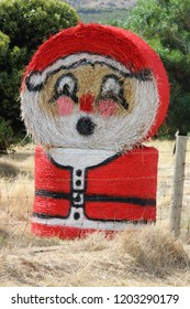 Santa Claus painted on round hay bales.
