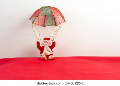 Santa Claus, parachute, sitting deep red. White background for your text space. Christmas card.