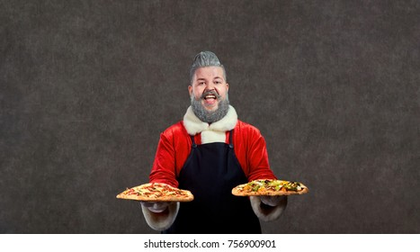 Santa Claus with pizza in hands smiling at the background copy space.