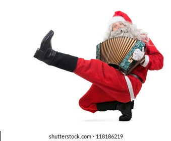 Santa Claus is playing music on the accordion when dancing cossack dance. Santa dancing traditional Russian dance, isolated on a white background. Christmas concert.