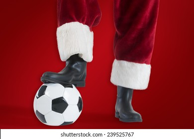 Santa Claus is playing soccer against red background