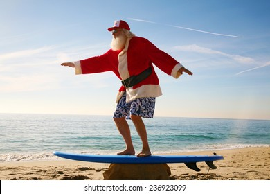 Santa Claus practices his Surfing Skills on his Surf Board on the beach, before he goes into the ocean. Santa Loves the Beach when on vacation from delivering gifts to good boys and girls at christmas